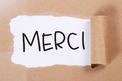 Merci, Motivational Words Quotes Concept. Merci, French thank you words letter, written on piece of memo paper. Motivational business typography quotes concept royalty free stock image