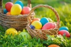 Merci nel carrello variopinte delle uova di Pasqua, sulla molla l'erba Fotografia Stock Libera da Diritti