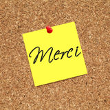 Merci. Note pinned on cork noticeboard stock photos