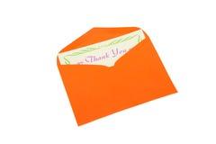Merci noter dans l'enveloppe orange sur le blanc photos stock