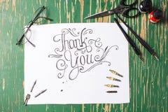 Merci noter la calligraphie avec l'équipement d'écriture photographie stock libre de droits