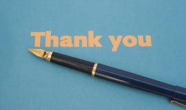 Merci noter sur le papier bleu avec le crayon lecteur. Images stock