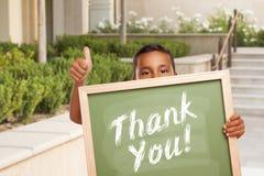 Merci panneau de craie tenu par le garçon hispanique renonçant à des pouces photo stock