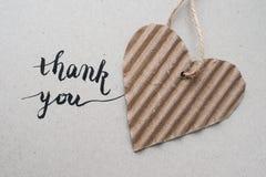 'merci' remettre le lettrage - calligraphie faite main et coeur avec le papier d'emballage Photos stock