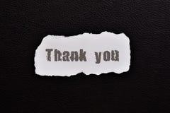 Merci sur le papier sur la peau texturisée foncée du texte photo stock