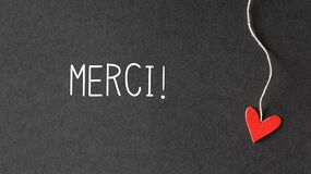 Merci - Thank you in French language with paper hearts