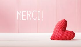 Merci - Thank you in French language with a red heart cushion