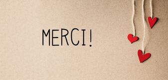 Merci - Thank you in French language with small hearts