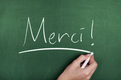 Merci. Woman hand writing merci note on green blackboard royalty free stock images