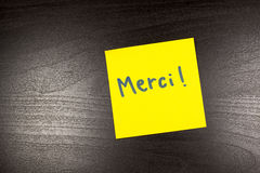 Merci' written on a yellow sticky note (thank you in French) on black background.  Stock Image