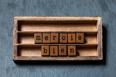 Mercie bien. Thank you very much written in French translation. Vintage box, wooden cubes phrase with old style letters. Gray stone textured background. Close stock images