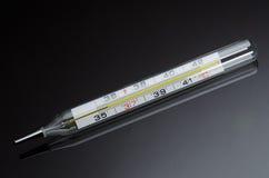 Mercury en el termómetro de cristal en fondo negro con la reflexión Foto de archivo libre de regalías