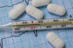 Mercury termometer och vitaminer på tabellen royaltyfria foton