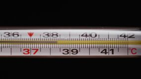 Mercury thermometer on black background. Temperature rises to 40 degrees Celsius