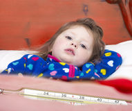 Mercury thermometer and a little sick girl Royalty Free Stock Photo