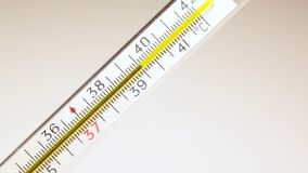 Mercury in thermometer moves on scale, showing patient's high temperature