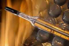 Mercury thermometer and tablets in fire Royalty Free Stock Photo