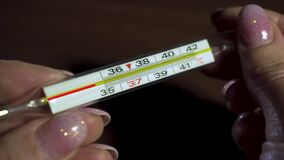 Mercury thermometer using animation shows temperature of 36.6 on woman hands during season of respiratory disease