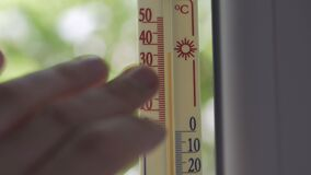 Mercury thermometer on the window, the temperature outside is 35 degrees Celsius