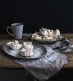 Merengue y taza blancos de chocolate caliente en una tabla de madera rústica Backdro negro Fotografía de archivo