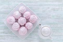 Merengues bonitas da rosa da cor pastel, zéfiros, marshmallows e um bule na tabela de madeira do vintage foto de stock royalty free