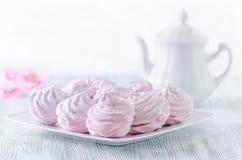 Merengues bonitas da rosa da cor pastel, zéfiros, marshmallows e um potenciômetro do café na tabela de madeira do vintage, flores fotos de stock royalty free