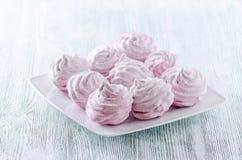 Merengues bonitas da rosa da cor pastel, zéfiros, marshmallows na tabela de madeira do vintage fotografia de stock