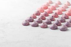 Merengues coloridos em cores roxo-cor-de-rosa em uma tabela branca Fotos de Stock