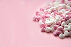 Merengues del rosa y blancos mini en la forma de los descensos, que mienten en un fondo rosado Lugar para el texto fotografía de archivo libre de regalías