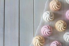 Merengues en colores pastel desde arriba en el papel de la hornada Imagen de archivo