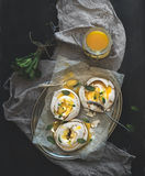 Merengues with lemon curd, fresh mint on silver tray, beige kitchen towel and grunge dark backdrop Stock Photos