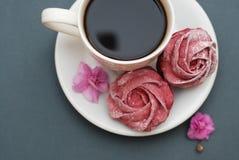 Merengues y taza de café rosados dulces en fondo del gris azul con las flores rosadas Fondo de la primavera con el espacio de la  Imagen de archivo