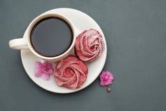 Merengues y taza de café rosados dulces en fondo del gris azul con las flores rosadas Fondo de la primavera con el espacio de la  Imagenes de archivo