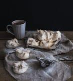 Merengues y taza de chocolate caliente en una tabla de madera rústica Fondo negro Imagen de archivo