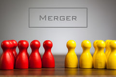 Merger concept with pawn figurines on table. Grey background Stock Images