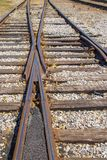 The merging of the tracks - two old rusty rail lines come together with a few fall leaves scattered among the gravel - selective. Focus stock photos