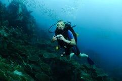 Mergulhador da mulher sobre o recife Foto de Stock
