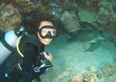 Mergulhador de sorriso pela tartaruga verde foto de stock royalty free