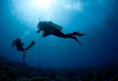 Mergulhador do mergulhador mostrado em silhueta de encontro ao sol Fotografia de Stock Royalty Free