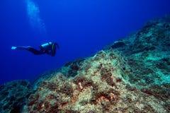 Mergulhador no recife de pedra subaquático foto de stock
