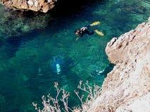 Mergulhadores de mergulhador dois abaixo e um na superfície no mar Mediterrâneo na costa de Sicília imagem de stock