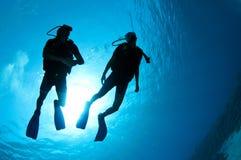 Mergulhadores de mergulhador mostrados em silhueta Fotografia de Stock