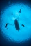 Mergulhadores de mergulhador que descem na água azul fotografia de stock royalty free
