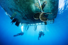 Mergulhadores de mergulhador sob o barco do mergulho Imagens de Stock Royalty Free