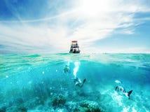 Mergulhadores e barco no mar das caraíbas Imagem de Stock