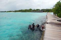 Mergulhadores no mar perto do cais da madeira em Maldivas Fotografia de Stock Royalty Free