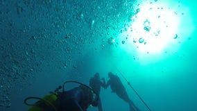 Mergulhadores que nadam debaixo d'água a pretensão aumentar para surgir, bolhas de ar na água filme