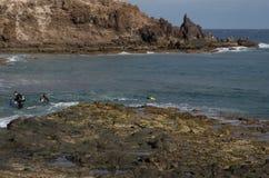 Mergulhadores que saem do mar fotografia de stock