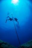 Mergulhadores sob o barco pelo tempo do deco no azul Imagens de Stock Royalty Free