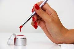 Mergulhando a escova nos vernizes para as unhas Foto de Stock